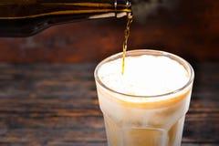 关闭啤酒涌入从棕色bottl的一块冻玻璃 免版税库存图片