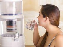 关闭喝一杯与水净化器过滤器系统的水的一名美丽的妇女在厨房背景的 免版税库存照片