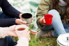关闭喝从杯子的远足者茶在阵营 免版税库存照片