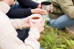 关闭喝从杯子的远足者茶在阵营 库存图片