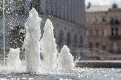 关闭喷泉的冷的干净的闪耀的透明淡水高强大涌出  白色泡沫和小滴在城市backgr 库存图片