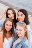关闭四个年轻美丽的女朋友画象在海滩的夏天 免版税库存图片