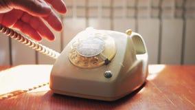 关闭回答男性的手拾起葡萄酒减速火箭的转台式电话的接收器和电话 股票录像