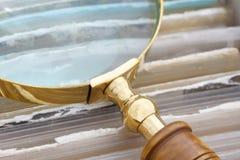 关闭在一个古色古香的金黄放大镜 免版税库存照片