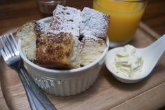 关闭在一个杯子的多士用在上面搽粉的糖粉,在快照的蜂蜜,投入木板材,木桌,早晨早餐 图库摄影