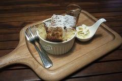 关闭在一个杯子的多士用在上面搽粉的糖粉,在快照的蜂蜜,投入木板材,木桌,早晨早餐 免版税库存照片