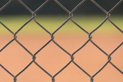 关闭在一个棒球场的篱芭与在背景中和外野弄脏的耕地 库存图片