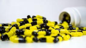 关闭在一个瓶掉下来的处方药 黑和黄色药片 免版税图库摄影