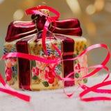 关闭在一个礼物盒的装饰圣诞节装饰品有红色丝带的 库存图片