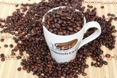 关闭在一个空白杯子的咖啡豆 免版税库存图片