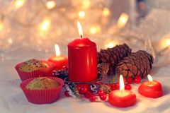 关闭在一个红色封皮的松饼与红色蜡烛和假日花圈 与浅景深的Bokeh背景 库存图片