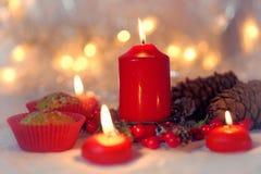 关闭在一个红色封皮的松饼与红色蜡烛和假日花圈 与浅景深的Bokeh背景 库存照片