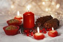 关闭在一个红色封皮的松饼与红色蜡烛和假日花圈 与浅景深的Bokeh背景 图库摄影