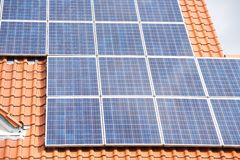 关闭在一个红色屋顶的太阳电池板 免版税库存图片