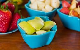 关闭在一个洋红色碗里面的一棵美味苹果用被分类的果子,草莓、梨、猕猴桃和片断  免版税库存照片