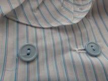 关闭在一件被剥离的女衬衫的蓝色按钮 免版税库存照片