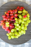 关闭在一块木板材的红色和gree葡萄 免版税库存图片