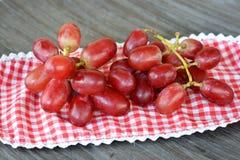 关闭在一块木板材的红葡萄 库存图片