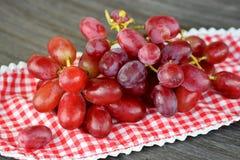 关闭在一块木板材的红葡萄 免版税库存图片
