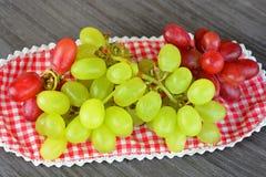 关闭在一块木板材的绿色和红葡萄 免版税库存图片