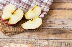 关闭在一张木桌上的一个切的红色苹果 免版税库存图片