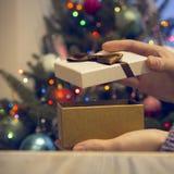 关闭在一张木桌上的手一个礼物盒反对装饰的圣诞树 库存照片