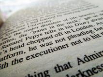 关闭在一本书的词与词'刽子手'在焦点 免版税库存照片