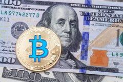 关闭在一百张钞票的金黄蓝色bitcoin 免版税库存图片