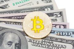 关闭在不同的美元钞票的金黄黄色bitcoin 免版税图库摄影