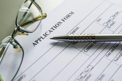 关闭在书桌上的一个工作申请书形式有笔和玻璃的 免版税库存图片