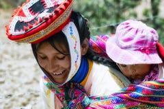 关闭在五颜六色的传统手工制造成套装备和运载她的吊索的婴孩打扮的一名微笑的盖丘亚族人的妇女的画象 库存图片