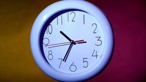 关闭在五颜六色的背景的一个白色时钟 股票录像