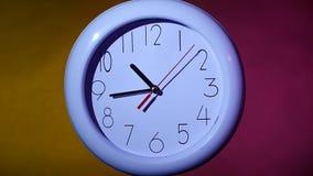 关闭在五颜六色的背景的一个白色时钟 股票视频