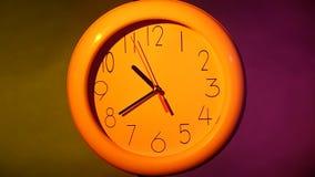 关闭在五颜六色的背景的一个黄色时钟 股票视频