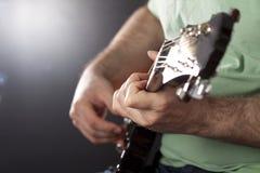 关闭在人弹吉他的` s手上 免版税库存图片