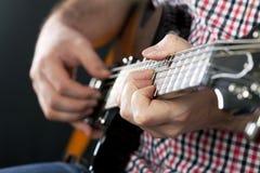 关闭在人弹吉他的` s手上 免版税库存照片