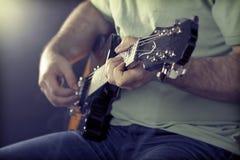 关闭在人弹吉他的` s手上 图库摄影