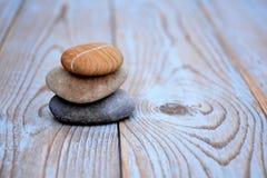 关闭在使用的木头的三块禅宗石头 免版税库存照片