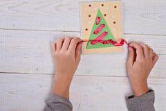 关闭在做圣诞树的儿童的手上由色纸 孩子艺术,艺术射出,手工制造新年装饰 图库摄影