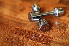 关闭在健身房的木棕色镶花地板上的镀铬物dumbells 库存图片