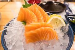 关闭在冰的三文鱼未加工的生鱼片在日本杯子用在木桌上的柠檬 免版税库存照片