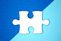 关闭在几何蓝色背景的白色难题片断 免版税图库摄影