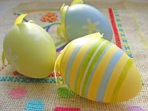 关闭在刺绣帆布的淡色黄色,蓝色和绿色复活节彩蛋 免版税库存图片