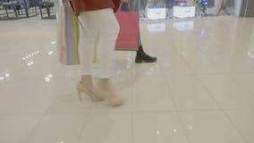 关闭在前进用时尚方式的脚跟的女性腿在购物中心,当运载的购物袋在他们的手上-时 影视素材
