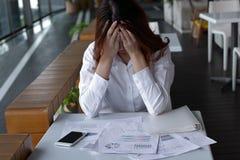 关闭在办公室注重了沮丧的年轻亚洲女商人覆盖物面孔用在书桌上的手 免版税库存照片