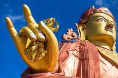 关闭在右金黄手用宗师仁波切雕象钉头锤和头,锡金的受护神宗师仁波切寺庙的 免版税库存照片