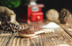 关闭在咖啡研磨的咖啡豆在匙子,葡萄酒下 免版税库存图片
