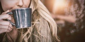 关闭在咖啡馆的妇女饮用的咖啡 免版税图库摄影