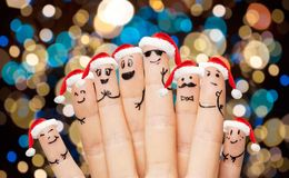 关闭在圣诞老人帽子的手指在圣诞节 免版税库存图片