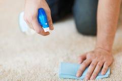 关闭在地毯的男性清洁污点 免版税图库摄影